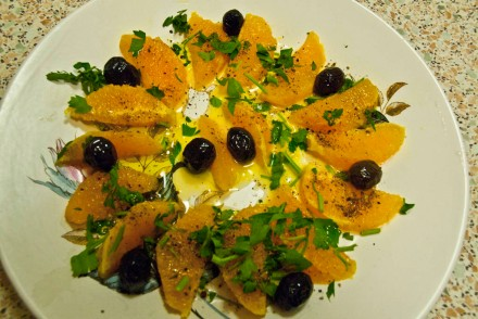 Oranges arranged prettily and sprinkled with olives, parsley, olive oil and pepper